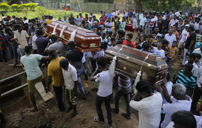 FILE - In this Tuesday, April 23, 2019, file photo, Sri Lankans carry the coffins carrying victims of the Easter Sunday bombings in Colombo, Sri Lanka. The U.S. ambassador says America had