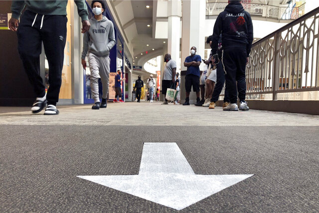 Shoppers walk near a social distancing arrow on a carpet in a hallway at Providence Place shopping mall, Monday, June 1, 2020, in Providence, R.I. Providence Place was opened Monday, June 1 for the first time since mid-March when it was closed in response to the coronavirus crisis. The mall has taken safety measures in response to the pandemic, including safe distancing signage and hand-sanitizing stations in common areas. (AP Photo/Steven Senne)