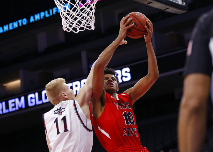 Fresno State forward Orlando Robinson, right, goes to the basket against Saint Mary's forward Matthias Tass during the second half of an NCAA college basketball game in Sacramento, Calif., Wednesday, Nov. 20, 2019. Saint Mary's won 68-58. (AP Photo/Rich Pedroncelli)