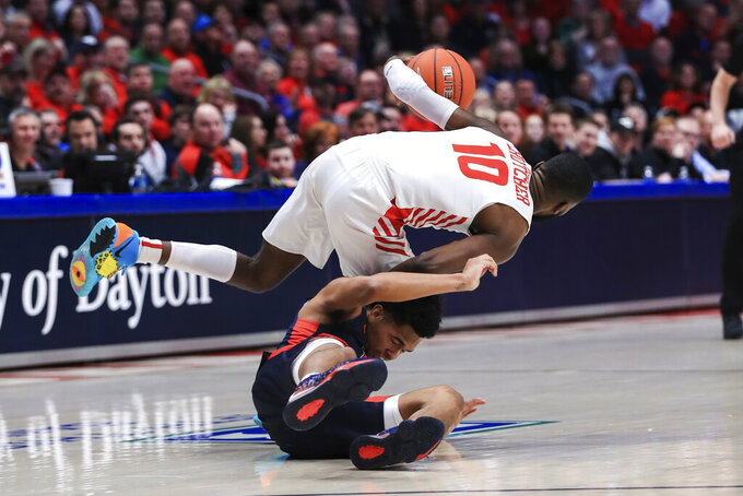 Dayton's Jalen Crutcher (10) controls the ball as he collides with Duquesne's Lamar Norman Jr. (4) in the first half of an NCAA college basketball game, Saturday, Feb. 22, 2020, in Dayton, Ohio. (AP Photo/Aaron Doster)