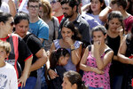 Neighbors of Argentine soccer player Emiliano Sala, wait for his remains to depart for Santa Fe after his wake in Progreso, Argentina, Saturday, Feb. 16, 2019. The Argentina-born forward died in an airplane crash in the English Channel last month when flying from Nantes in France to start his new career with English Premier League club Cardiff. (AP Photo/Natacha Pisarenko)