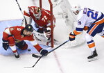 Florida Panthers goaltender Sergei Bobrovsky (72) stops a wrap-a-round attempt from New York Islanders center Brock Nelson (29) as defenseman Anton Stralman (6) keeps close during the first period of an NHL Stanley Cup playoff hockey game in Toronto, Ontario, Wednesday, Aug. 5, 2020. (Nathan Denette/The Canadian Press via AP)