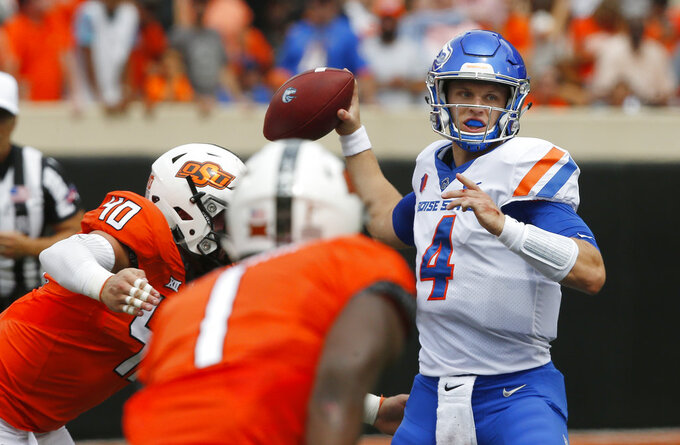 Boise State quarterback Brett Rypien (4) throws under pressure from Oklahoma State defensive end Brock Martin (40) and linebacker Calvin Bundage (1) in the first half of an NCAA college football game in Stillwater, Okla., Saturday, Sept. 15, 2018. (AP Photo/Sue Ogrocki)