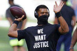 "Seattle Seahawks quarterback Russell Wilson wears a T-shirt that reads ""We Want Justice"" in support of Black Lives Matter as he warms up before an NFL football game against the New England Patriots, Sunday, Sept. 20, 2020, in Seattle. (AP Photo/Elaine Thompson)"