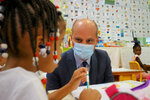French Education Minister Jean-Michel Blanquer talks with a child for the first day at the elementary school of Louis de Frontenac in Chateauroux, central France, Tuesday Sept.1, 2020. Millions of French children starting going back to class Tuesday despite a recent rise in virus infections, in a nationwide experiment aimed at bridging inequalities and reviving the economy. (Guillaume Souvant, Pool via AP)