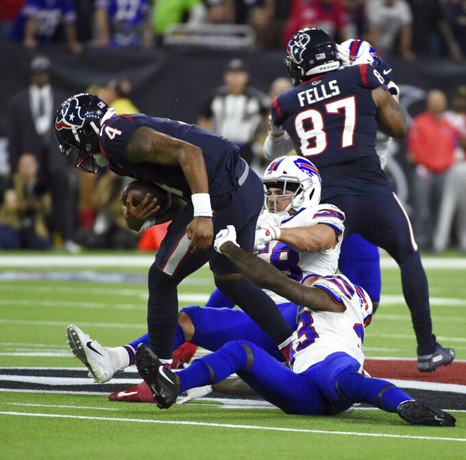 Houston Texans quarterback Deshaun Watson (4) breaks away from Buffalo Bills' Siran Neal (33) and Matt Milano (58) to throw a pass to setup the game-winning field goal during overtime of an NFL wild-card playoff football game Saturday, Jan. 4, 2020, in Houston. The Texans won 22-19 in overtime. (AP Photo/Eric Christian Smith)