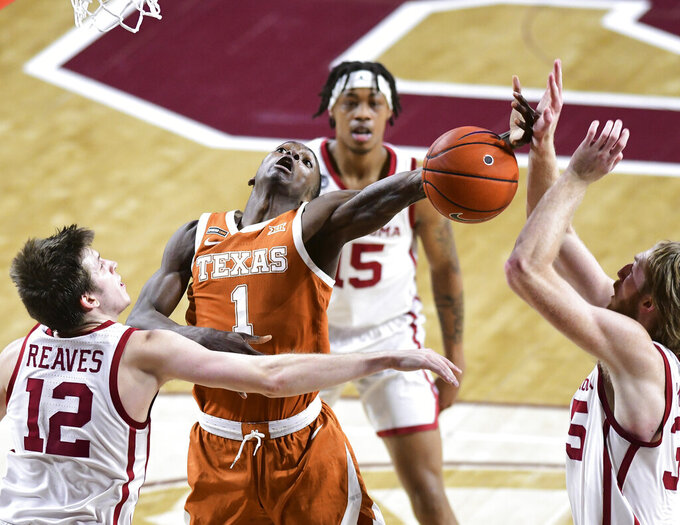 Texas guard Andrew Jones (1) is fouled on a shoOklahoma guard Austin Reaves (12) and forward Brady Manek, right, defend during the first half of an NCAA college basketball game in Norman, Okla., Thursday, March 4, 2021. (AP Photo/Kyle Phillips)