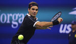 FILE - In this Sept. 3, 2019, file photo, Roger Federer, of Switzerland, chases a shot from Grigor Dimitrov, of Bulgaria, during the quarterfinals of the U.S. Open tennis tournament in New York. The Swiss government said it will produce a 20 franc silver coin with Federer's image on it. It is the first time Switzerland has dedicated a commemorative coin to a living person. (AP Photo/Charles Krupa, File)