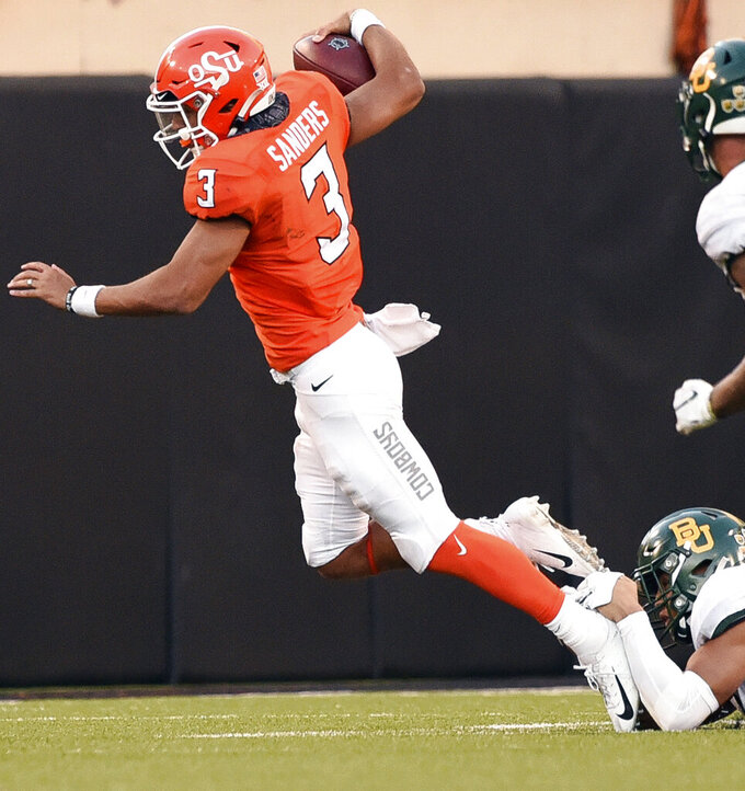 Oklahoma State quarterback Spencer Sanders (3) is brought down by the ankle tackle of Baylor linebacker Blake Lynch, bottom right, during the second half of an NCAA college football game in Stillwater, Okla., Saturday, Oct. 19, 2019. (AP Photo/Brody Schmidt)
