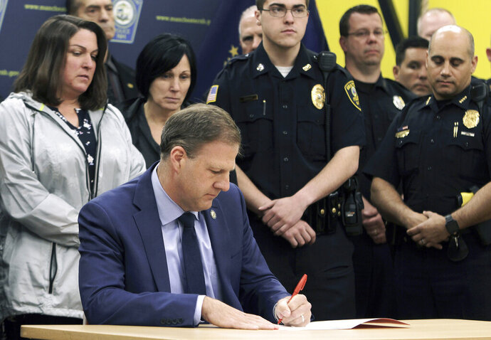 FILE - In this May 3, 2019 file photo, New Hampshire Gov. Chris Sununu vetoes a bill that would repeal the death penalty in the state during an event at the Officer Michael Briggs Community Center in Manchester, N.H. Through mid-July, Sununu had vetoed 30 bills this year, more than quadruple his total for his first two years in office combined. (Nick Stoico/The Concord Monitor via AP, File)