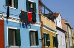 In this image taken on Thursday, Jan. 16, 2020, an elderly woman hangs laundry outside a window, at the Burano island, Italy. The Venetian island of Burano's legacy as a fishing village remains the source of its charms: the small colorful fishermen's cottages, traditional butter cookies that were the fishermen's sustenance at sea and delicate lace still stitched by women in their homes. As the island's population dwindles, echoing that of Venice itself, so too are the numbers of skilled artisans and tradespeople who have kept the traditions and economy alive. (AP Photo/Luca Bruno)