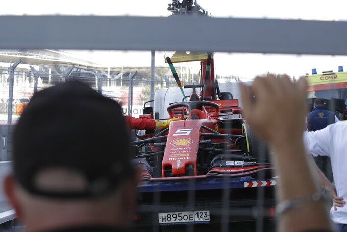The racer car of Ferrari driver Sebastian Vettel of Germany is towed by mechanics at pit during the Russian Formula one Grand Prix, at the 'Sochi Autodrom' Formula One circuit, in Sochi, Russia, Sunday, Sept. 29, 2019. (AP Photo/Luca Bruno)