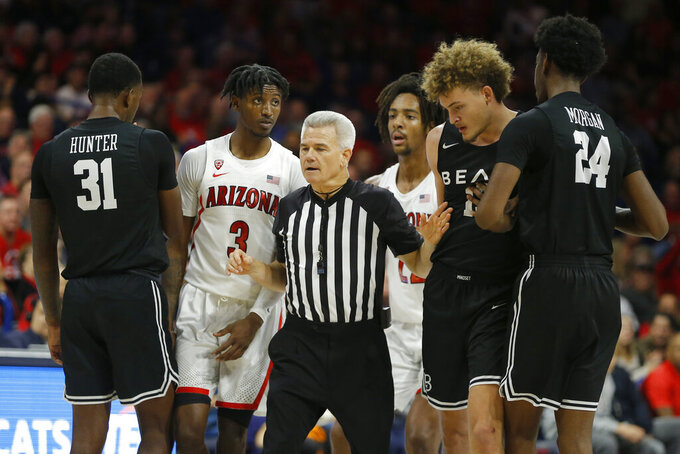 NCAA official Larry Spaulding breaks up Arizona guard Dylan Smith (3) and Long Beach State forward Romelle Mansel (13) after an altercation in the second half during an NCAA college basketball game, Sunday, Nov. 24, 2019, in Tucson, Ariz. Arizona defeated Long Beach State 104-67. (AP Photo/Rick Scuteri)