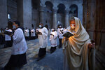 Priests circle the Edicule during Easter Sunday Mass led by the Latin Patriarch at the Church of the Holy Sepulchre, traditionally where many Christians believe Jesus Christ was crucified, buried and rose from the dead, in the Old City of Jerusalem, Sunday, April 4, 2021. (AP Photo/Oded Balilty)