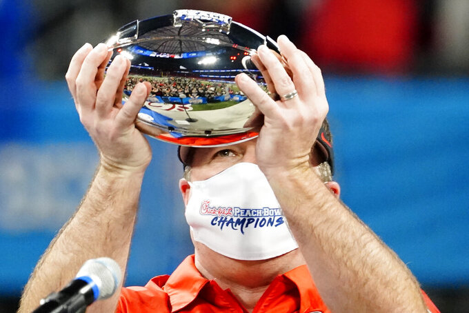 Georgia head coach Kirby Smart hold the championship trophy after the Peach Bowl NCAA college football game against Cincinnati, Friday, Jan. 1, 2021, in Atlanta. Georgia won 22-21. (AP Photo/Brynn Anderson)