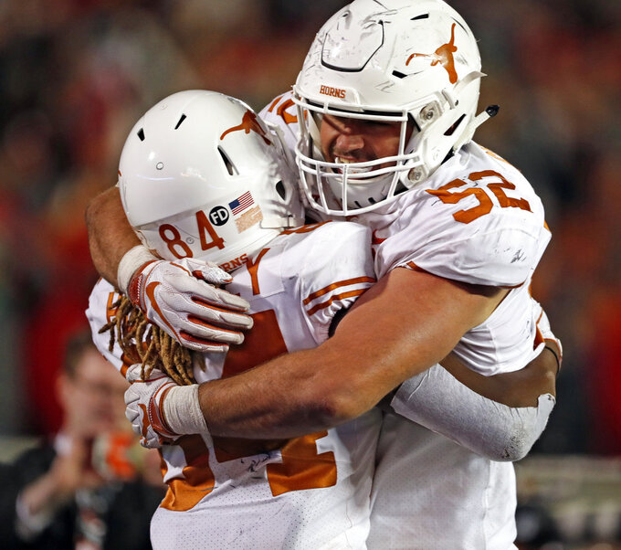 Texas' Lil'Jordan Humphrey (84) celebrates with Samuel Cosmi (52) after scoring the go-ahead touchdown during the second half of an NCAA college football game against Texas Tech, Saturday, Nov. 10, 2018, in Lubbock, Texas. (AP Photo/Brad Tollefson)
