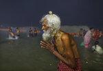 An elderly pilgrim prays after a holy dip at the Sangam in Prayagraj, India, Thursday, Feb. 11, 2021. (AP Photo/Rajesh Kumar Singh)