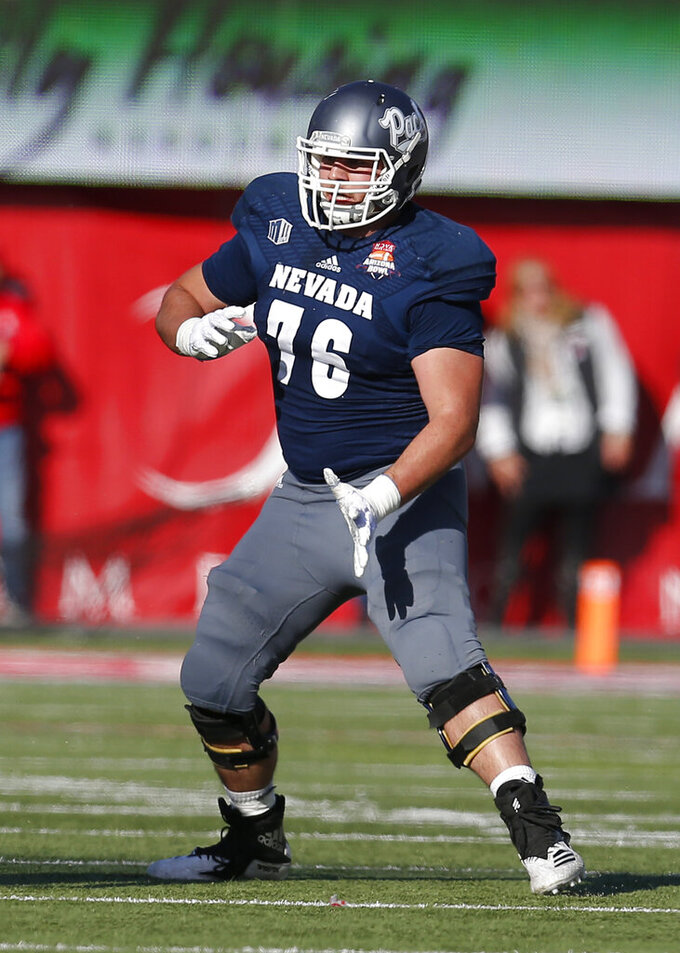 "FILE - In this Dec. 29, 2018 file photo, Nevada offensive lineman Nate Brown (76) plays in the first half of an NCAA college football bowl game against Arkansas State in Tucson, AZ. Football players and other college athletes are facing challenges when it comes to following nutrition plans amid the coronavirus pandemic.  Brown says athletes who ""really take care of their nutrition"" will be in better shape whenever they can return to campuses following the pandemic.  (AP Photo/Rick Scuteri, File )"