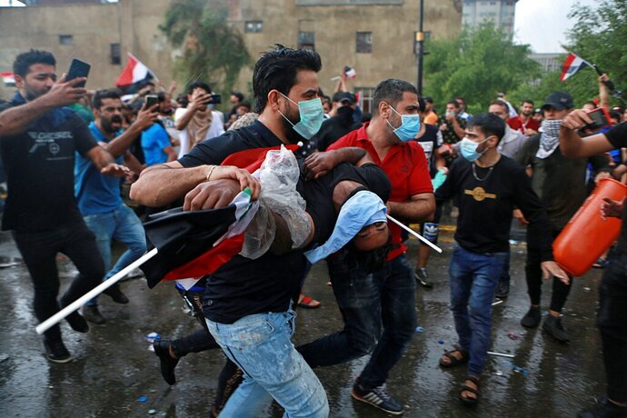 An injured protestor is rushed to a hospital during a demonstration in central Baghdad, Iraq, Friday, Oct. 25, 2019. Iraqi police fired live shots into the air as well as rubber bullets and dozens of tear gas canisters on Friday to disperse thousands of protesters on the streets of Baghdad, sending young demonstrators running for cover and enveloping a main bridge in the capital with thick white smoke. (AP Photo/Khalid Mohammed)
