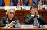 Romanian Prime Minister Viorica Dancila, left, looks at her mobile phone as vice premier Daniel Suciu wipes his face ahead of a no confidence vote in Bucharest, Romania, Thursday, Oct. 10, 2019. Romania's Social Democrat government has lost a vote of no-confidence in Parliament after lawmakers voted 238-4 against Prime Minister Viorica Dancila's government. (AP Photo/Vadim Ghirda)
