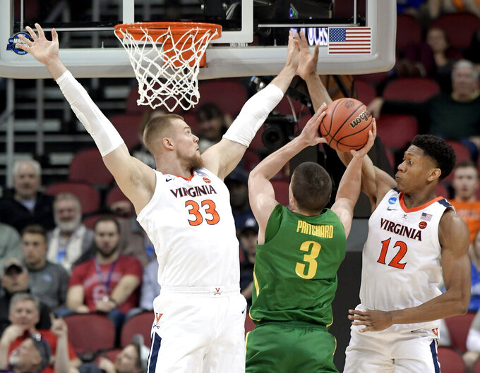 Oregon's Payton Pritchard (3) drives against Virginia's Jack Salt (33) and De'Andre Hunter (12) during the second half of a men's NCAA Tournament college basketball South Regional semifinal game, Thursday, March 28, 2019, in Louisville, Ky. (AP Photo/Timothy D. Easley)