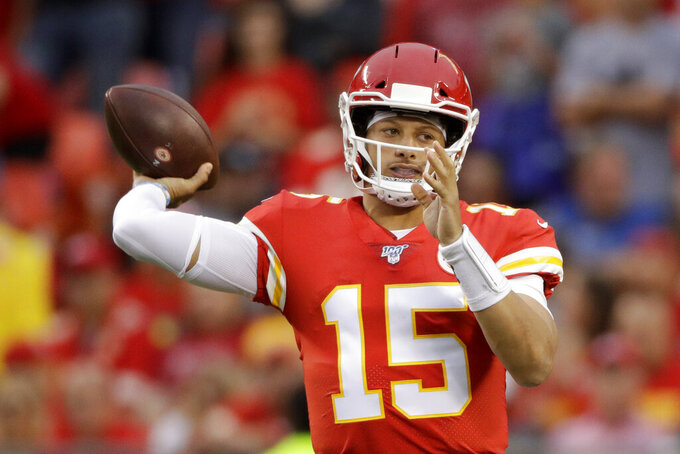 Kansas City Chiefs quarterback Patrick Mahomes (15) throws a touchdown pass to running back Damien Williams during the first half of an NFL preseason football game against the San Francisco 49ers in Kansas City, Mo., Saturday, Aug. 24, 2019. (AP Photo/Charlie Riedel)