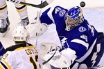Tampa Bay Lightning goaltender Andrei Vasilevskiy (88) misses the puck shot from Boston Bruins center Charlie Coyle (13) during the first period of an NHL Stanley Cup Eastern Conference playoff hockey game in Toronto, Ontario, Sunday, Aug. 23, 2020. (Frank Gunn/The Canadian Press via AP)