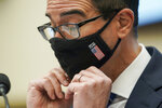 Treasury Secretary Steven Mnuchin adjusts his face mask during a House Financial Services Committee hearing on Capitol Hill in Washington, Wednesday, Dec. 2, 2020. (Greg Nash/Pool via AP)