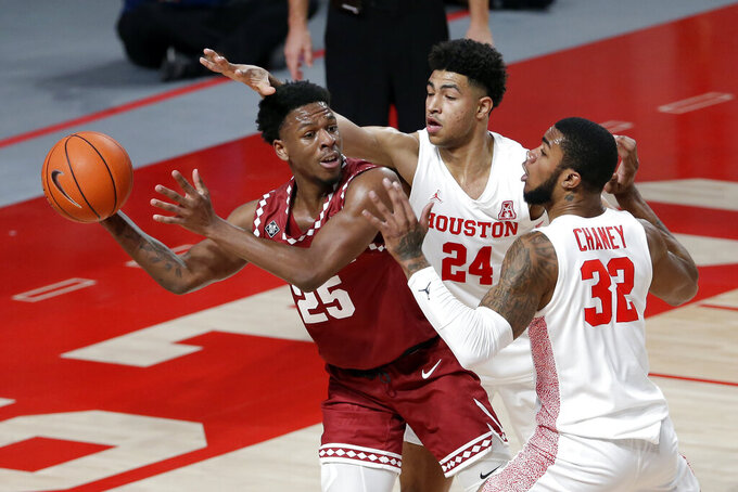 Temple guard Jeremiah Williams (25) looks to pass the ball under pressure from Houston guard Quentin Grimes (24) and forward Reggie Chaney (32) during the first half of an NCAA college basketball game Tuesday, Dec. 22, 2020, in Houston. (AP Photo/Michael Wyke)