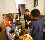 Fadumo Hussein, 45, left, talks with her friend, Pam Lang, center, and grandson, Rashed Mohammed, 4, at Hussein's home in Columbus, Ohio on Friday, Feb. 23, 2018. Hussein, a Muslim refugee from Somalia, has been separated from her elderly parents, who are in Africa and having difficulty getting to the U.S. because of President Trump's travel ban. She met Lang when her daughters, including Afnan Salem, background, helped Lang and other members of a church with a homework program for refugees.