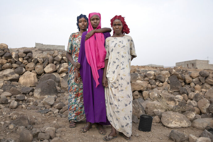 In this July 12, 2019 photo, teenagers, from right, Hamdiya, Ikram, and Safeya, pose for a portrait at a slum where they took shelter after entering the country making it the first stop of their journey, north of the border with Ethiopia, in Dikhil, Djibouti. The 100-mile (120-kilometer) trip across Djibouti can take days. Many migrants end up in the country's capital, also named Djibouti, living in slums and working to earn money for the crossing. Young women often are trapped in prostitution or enslaved as servants. (AP Photo/Nariman El-Mofty)