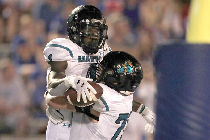 Coastal Carolina running back CJ Marable (1) celebrates his touchdown with offensive lineman Ethan Howard (75) during the second half of an NCAA college football game against Kansas in Lawrence, Kan., Saturday, Sept. 7, 2019. (AP Photo/Orlin Wagner)