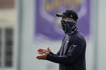 Baltimore Ravens head coach John Harbaugh wears a face mask to protect against COVID-19 as he encourages his team warming up during an NFL football camp practice, Monday, Aug. 17, 2020, in Owings Mills, Md. (AP Photo/Julio Cortez)