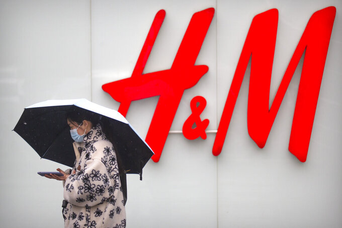 A woman walks by an H&M clothing store at a shopping mall in Beijing on March 26, 2021. An American business group warned Tuesday, May 11, 2021 that government-instigated consumer boycotts of foreign shoe, clothing and other brands in China are making companies less willing to invest. Brands including Swedish retailer H&M, Adidas and Nike have been targeted by demands online for consumer boycotts. That came after state media criticized them for expressing concern about reports of possible forced labor by ethnic minorities in the Xinjiang region of China's northwest. (AP Photo/Mark Schiefelbein)