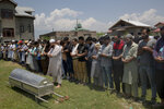Relatives and neighbors offer prayers near the coffin of civilian Bashir Ahmed Khan, during his funeral on the outskirts of Srinagar, Indian controlled Kashmir, Wednesday, July 1, 2020. Suspected rebels attacked paramilitary soldiers in the Indian portion of Kashmir, killing Khan and a paramilitary soldier, according to government sources. The family refutes the claim. (AP Photo/ Dar Yasin)