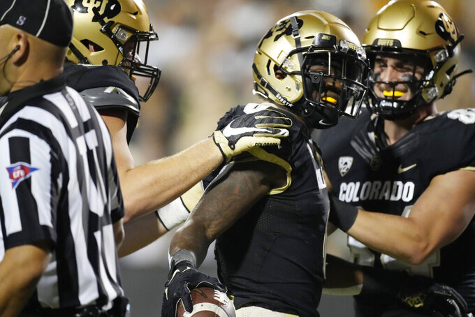Colorado running back Ashaad Clayton, center, is congratulated after his touchdown run against Northern Colorado during the second half of an NCAA college football game Friday, Sept. 3, 2021, in Boulder, Colo. Colorado won 35-7. (AP Photo/David Zalubowski)