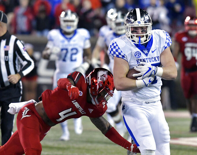 Louisville safety TreSean Smith (4) attempts to tackle Kentucky tight end C.J. Conrad (87) during the first half of an NCAA college football game in Louisville, Ky., Saturday, Nov. 24, 2018. (AP Photo/Timothy D. Easley)