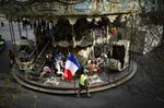 A man carrying a French national flag walks past a carousel near Sacre Coeur in Paris, Saturday, March 23, 2019. The French government vowed to strengthen security as yellow vest protesters stage a 19th round of demonstrations, in an effort to avoid a repeat of last week's riots in Paris. (AP Photo/Kamil Zihnioglu)