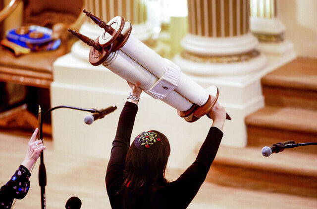 FILE - In this Feb. 1, 2020, file photo, Rabbi Jacqueline Mates-Muchin holds a Torah scroll aloft during Shabbat morning service at Temple Sinai in Oakland, Calif. The California Department of Public Health released Monday, May 25, a framework under which county health departments can approve the reopening of churches, mosques, synagogues and other houses of worship that have mostly shuttered their doors since Gov. Gavin Newsom's March stay-at-home order designed to slow the spread of the coronavirus. (AP Photo/Noah Berger, File)