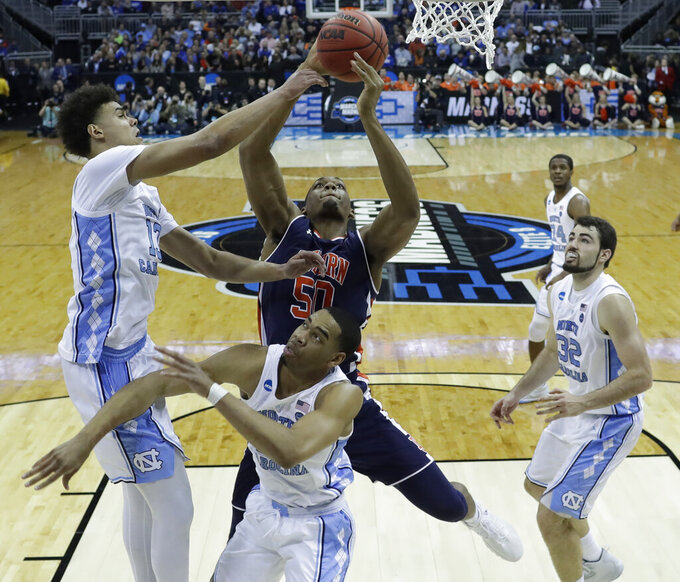 Auburn's Austin Wiley (50) shoots as North Carolina's Cameron Johnson, left, Garrison Brooks and Luke Maye (32) defend during the first half of a men's NCAA tournament college basketball Midwest Regional semifinal game Friday, March 29, 2019, in Kansas City, Mo. (AP Photo/Orlin Wagner)