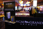 Hand sanitizer and disposable gloves are available at the main entrance to the MGM Grand Detroit casino, Wednesday, Aug. 5, 2020, in Detroit. Detroit's three casinos will start reopening Wednesday under new governor-mandated capacity restrictions, months after closing for the coronavirus pandemic. MotorCity Casino Hotel and the Greektown Casino-Hotel opened Wednesday. MGM Grand Detroit will open for invite-only VIP customers Wednesday and Thursday, and at 10 a.m. Friday for the general public. (AP Photo/Carlos Osorio)