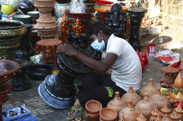 An artist wearing face mask as a precaution against the coronavirus gives final touches to decorative items ahead of Diwali, in Hyderabad, India, Wednesday, Nov. 11, 2020. Health officials have warned about the potential for the coronavirus to spread during the upcoming religious festival season, which is marked by huge gatherings in temples and shopping districts. (AP Photo/Mahesh Kumar A.)
