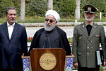 In this photo released by an official website of the office of the Iranian Presidency, President Hassan Rouhani, center, speaks during a media briefing after a cabinet meeting, as senior Vice President Eshaq Jahangiri, left, and Defense Minister Gen. Amir Hatami listen, in Tehran, Iran, Monday, March 18, 2019. On Monday Rouhani urged Iranians to put a curse on the United States, Israel and Saudi Arabia -- blaming America and its allies for his country's ailing economy. (Iranian Presidency Office via AP)