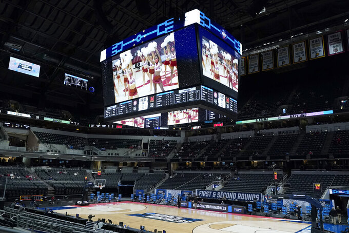 A performance by the Alabama cheerleaders is shown on the scoreboard during the first half of a college basketball game between Alabama and Maryland in the second round of the NCAA tournament at Bankers Life Fieldhouse in Indianapolis Monday, March 22, 2021. Since school cheerleaders and dance teams are not allowed at the tournament, video performances are the only way they can be presented. (AP Photo/Mark Humphrey)