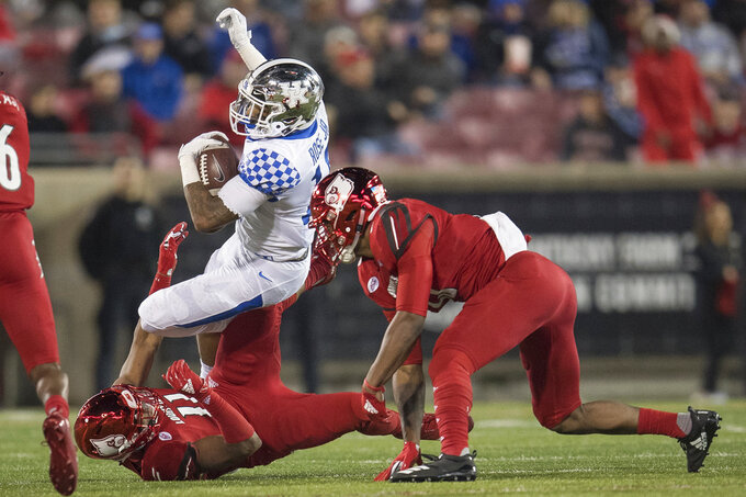 Kentucky running back Asim Rose (10) is tackled by Louisville safety Dee Smith (11) during the second half of an NCAA college football game in Louisville, Ky., Saturday, Nov. 24, 2018. (AP Photo/Bryan Woolston)