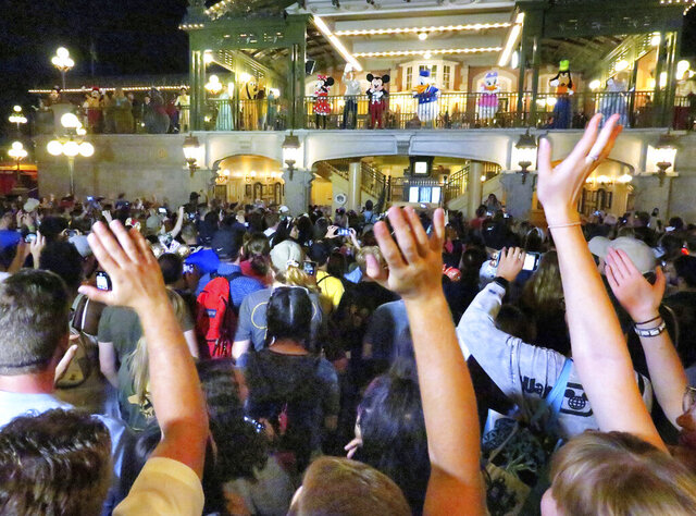 Guests wave goodbye to Mickey Mouse and friends on Main Street USA, in the Magic Kingdom at Walt Disney World, after the characters made a surprise appearance in the final minutes before the park closed, Sunday night, March 15, 2020, in Lake Buena Vista, Fla. Walt Disney World announced that all their Florida parks will be closed for the rest of March as a result of the coronavirus pandemic. (Joe Burbank/Orlando Sentinel)