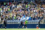 Seattle Seahawks cornerback Ugo Amadi carries the 12 flag out to cheering fans before playing a mock game as part of an NFL football training camp at Lumen Field in Seattle, Sunday, Aug. 8, 2021. (Bettina Hansen/The Seattle Times via AP)