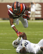 Virginia Tech wide receiver Tayzion Robinson (83) dives over Old Dominion defender Tobias Moss (18) in the first half of an NCAA college football game  in Blacksburg Va,. Saturday, Sept. 7, 2019. (Matt Gentry/The Roanoke Times via AP)
