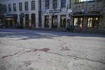 Blood stains remain on 6th Street after an early morning shooting on Saturday, June 12, 2021 in downtown Austin, Texas. Authorities say someone opened fire on the busy entertainment district wounding several people before getting away. (Aaron Martinez/Austin American-Statesman via AP)