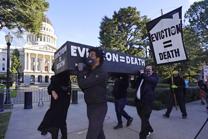 FILE — In this Jan. 25, 2021, file photo, demonstrators call passage of rent forgiveness and stronger eviction protections legislation and carry a mock casket past the Capitol in Sacramento, Calif. California Gov. Gavin Newsom and state legislative leaders are negotiating about whether to extend the state's ban on evictions for unpaid rent. California's eviction protections will expire on June 30. Newsom has proposed using federal coronavirus aid money to pay off 100% of the rent people owe. (AP Photo/Rich Pedroncelli, File)